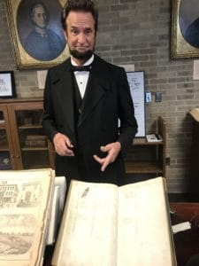 Michael Krebs as Abraham Lincoln with the Lincoln signed Randolph Hotel registry in Macomb's WIU Archives